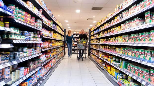 Ein Paar schiebt einen Einkaufswagen durch den Supermarkt