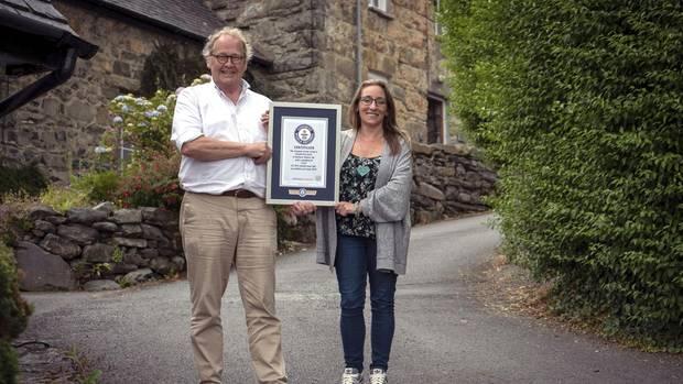 Gwyn Headley (l) und Sarah Badhan in der Straße Ffordd Pen Llech mit einer Urkunde des Guinness-Buches der Rekorde