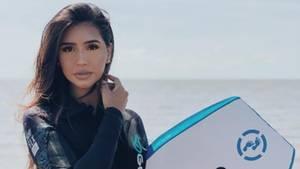 Die 21-jährige Aysha Khan posiert im Neoprenanzug mit Surfbrett
