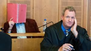 Der Angeklagte (hinten) sitzt mit Rechtsanwalt Philipp Berndtsen vor Prozessbeginn im Gerichtssaal des Landgerichtes