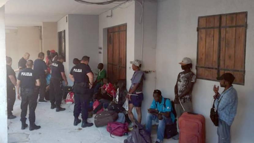 Polizisten und Migranten vor der Unterkunft in einemehemaligen Pferdestall.