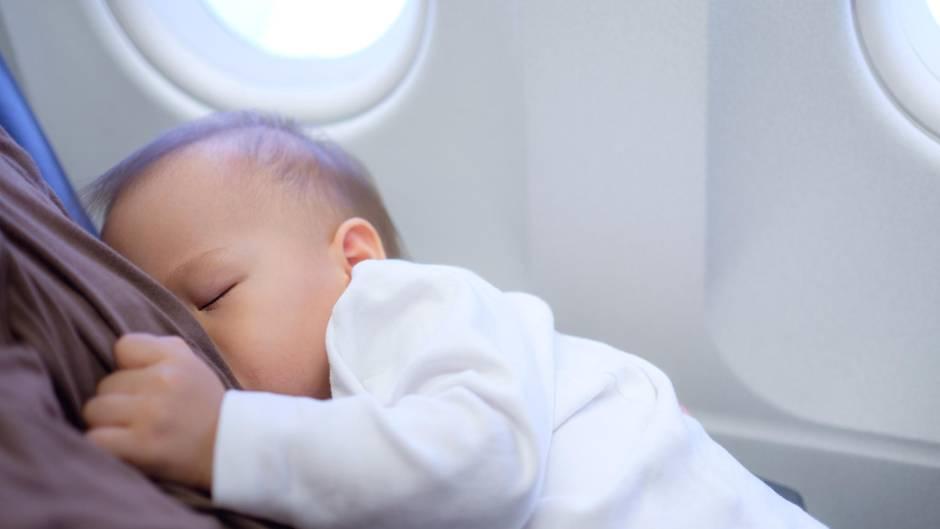 Eine Mutter stillt ihr Baby im Flugzeug