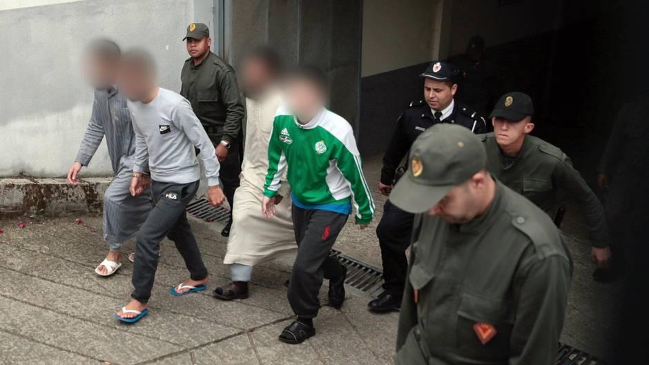 Vier der Tatverdächtigen werden von Sicherheitskräften aus dem Gerichtsgebäude begleitet (Archivbild)
