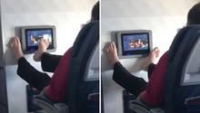 Mann bedient Entertainment-System im Flieger mit den Füßen