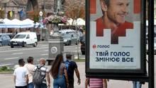 In Kiev gehen Menschen an einem Wahlplakat vorbei