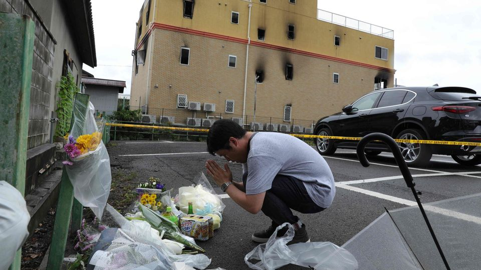 Ein Mann betet vor dem Gebäude, in dem 33 Menschen den Tod fanden
