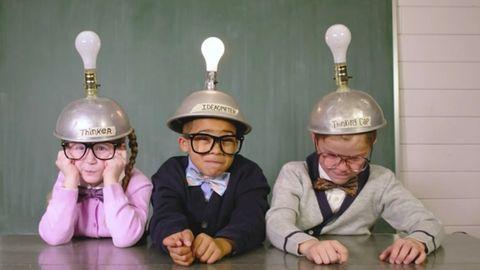 Drei Kinder mit Helmen und Glühbirnen auf dem Kopf