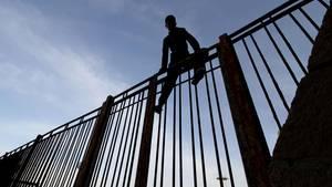 Migrant auf dem Grenzzaun zu Melilla