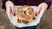 Abnehmen Kalorien: Eine Frau hält einen Bagel in der Hand