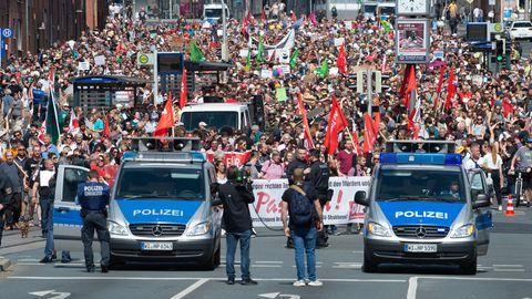 Kassel: Teilnehmer einer Gegendemonstration gehen mit Plakaten und Flaggen durch die Stadt
