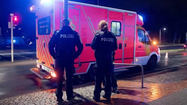 Zwei Polizeibeamte stehen vor einem Rettungswagen (Symbolbild)