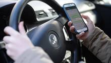 Eine Person hält während des Autofahrens ein Handy in der Hand
