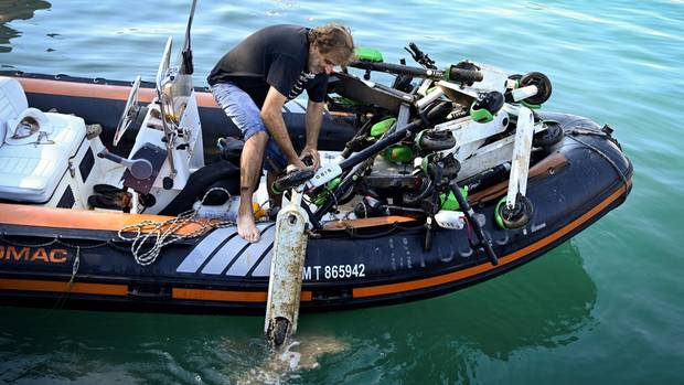 Ein Mann steht auf einem Boot und zieht einen E-Roller aus dem Wasser