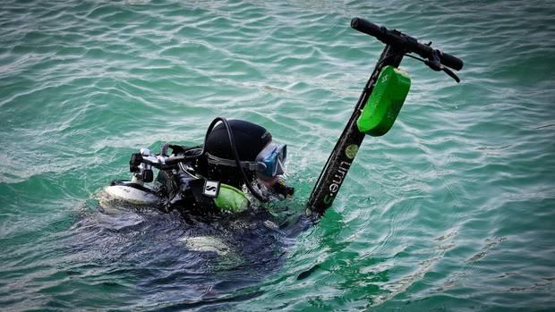 Ein Taucher birgt einen Roller aus dem Wasser