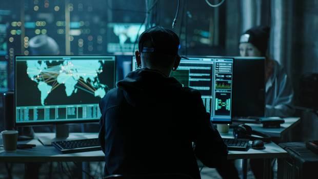 Junge Hacker sitzen in einem abgedunkelten Raum vor Bildschirmen