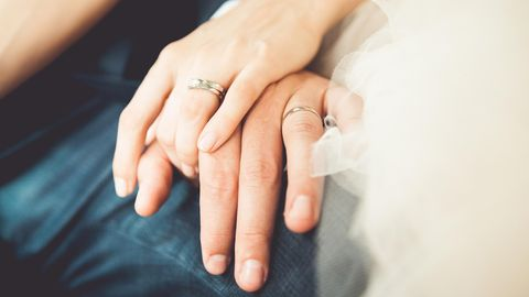 Zwei Hände mit Eheringen liegen liebevoll aufeinander