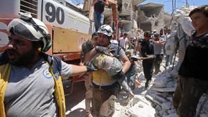 Mitglieder der Weißhelme tragen ein verletztes Kind aus den Trümmern