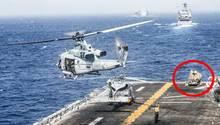 Auf der Landefläche des Kampfschiffs hebt ein Hubschrauber ab. Im Hintergrund steht das LMADIS-System