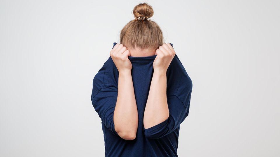 Frau versteckt sich unter Pullover