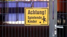 """Einfahrt zu einer Kindertagesstätte in Leipzig mit einem Schild """"Achtung, spielende Kinder"""""""