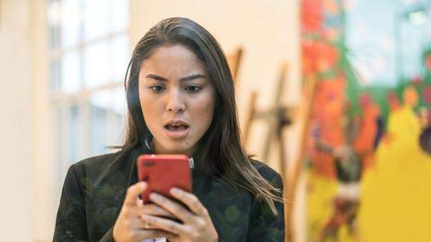 Eine Frau schaut überrascht auf ihr Smartphone