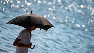 Niedersachsen, Göttingen: Ein Mann schützt sich am Kiessee mit einem Regenschirm vor der Sonne.