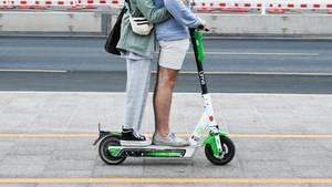 E-Scooter: Zwei junge Menschen fahren gemeinsam auf einem Roller