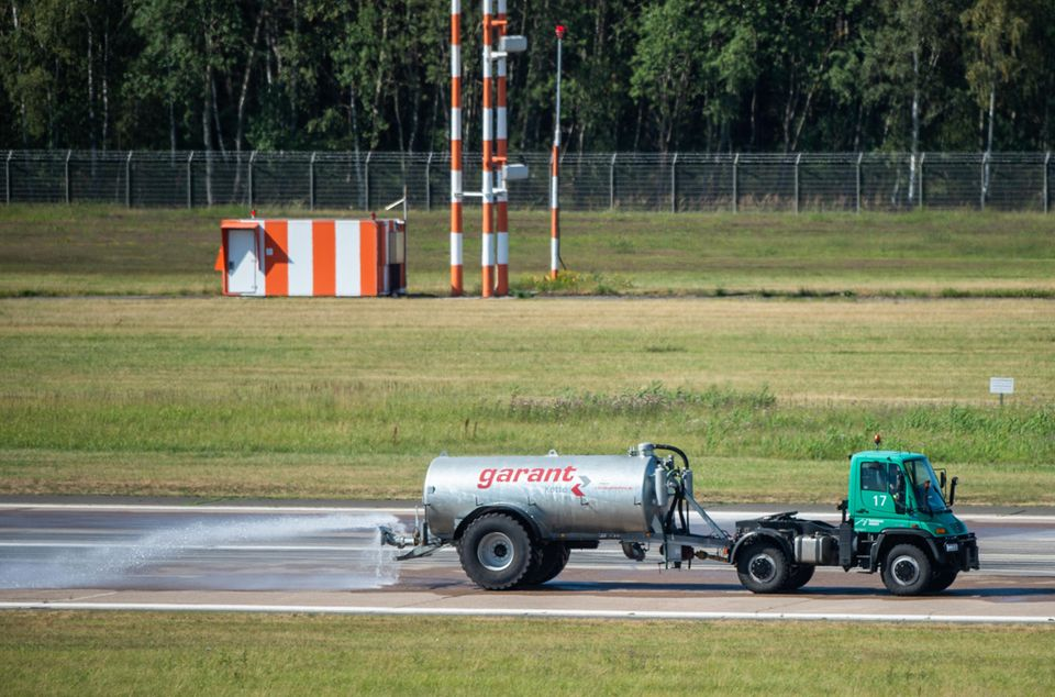 Hitzewelle in Deutschland – Tankwagen sprüht Wasser auf eine Landebahn in Hannover