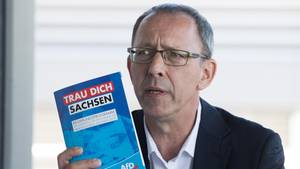 """Jörg Urban, Vorsitzender der AfD in Sachsen, hält eine Broschüre mit der Aufschrift """"Trau Dich Sachsen"""""""