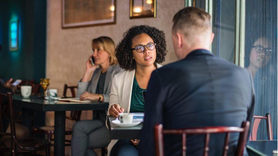 Mann mit Anzug sitzt auf einem Stuhl gegenüber einer Frau mit Brille, die mit ihm spricht