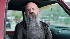 Sky sitzt mit langem grauen Bart und Lederjacke im Auto