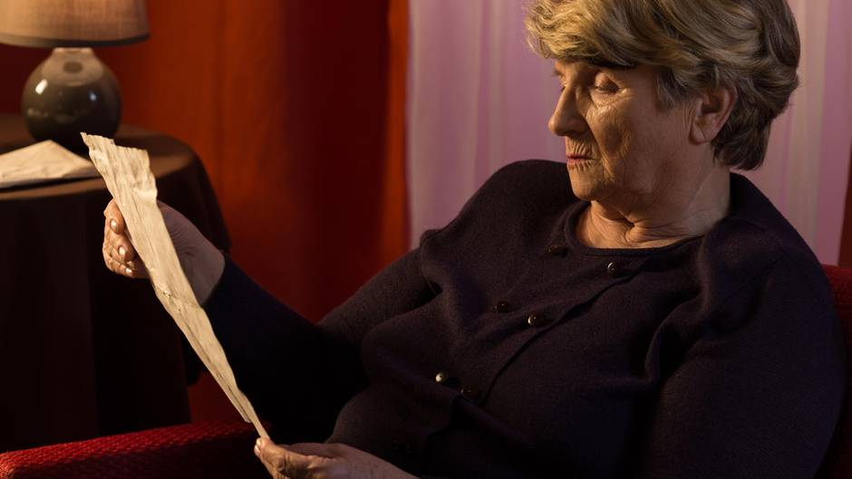 Eine Seniorin hält einen Brief in den Händen