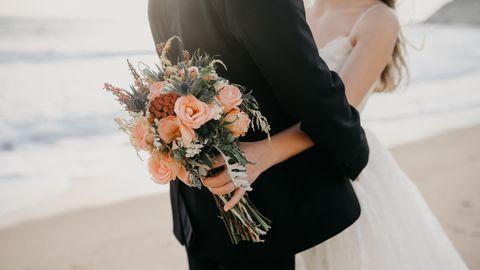Eine Frau und ein Mann in Hochzeitskleidung umarmen sich innig