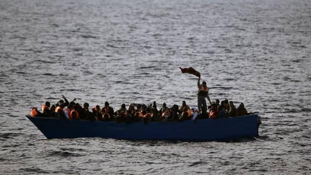 Migranten sitzen in einem Boot