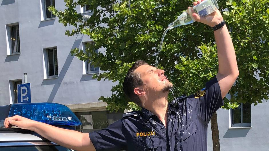 Ein Polizist gießt sich eine Flasche Wasser über das Gesicht