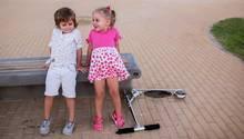 Ein Junge und ein Mädchen unterhalten sich draußen auf einer Bank