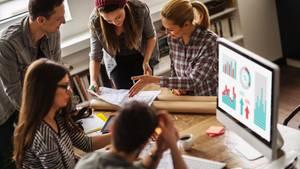 Fünf junge Menschen sitzen an einem Tisch und diskutieren über einen Plan