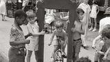 Kinder spielen und Erwachsene plaudern auf dem Bürgersteig