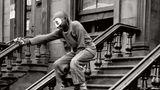 Ein maskierter Junge steht auf der Treppe eines Hauseingangs