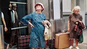 Zwei alte Damen mit Koffern am Straßenrand