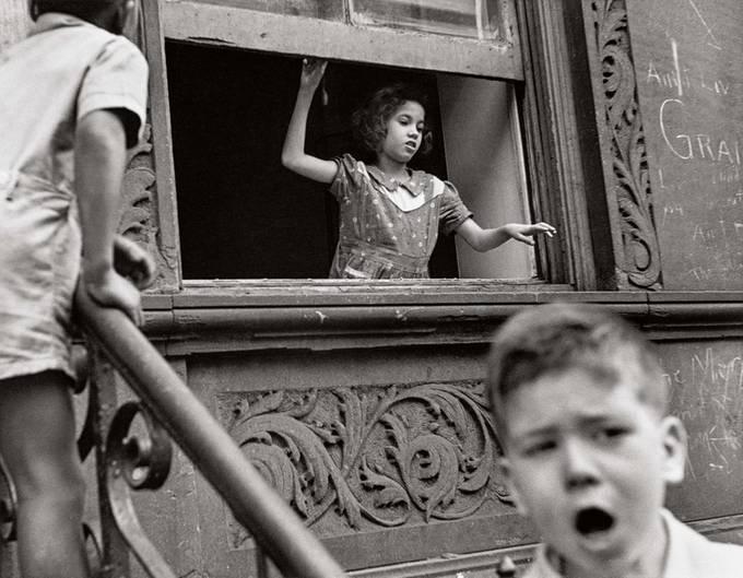 Ein Mädchen unterhält sich aus dem Fenster ihrer Wohnung mit Kindern auf der Straße