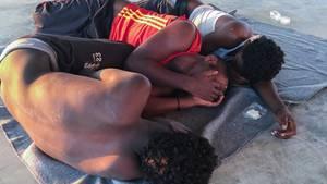 Die Aufnahme zeigt drei gerettete Bootsflüchtlinge, die verzweifelt in einem Migrantenlager in Libyen gestrandet sind.