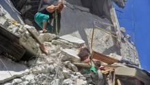 Zwei Kleinkinder versuchen, sich aus einem zerstörten Haus zu befreien