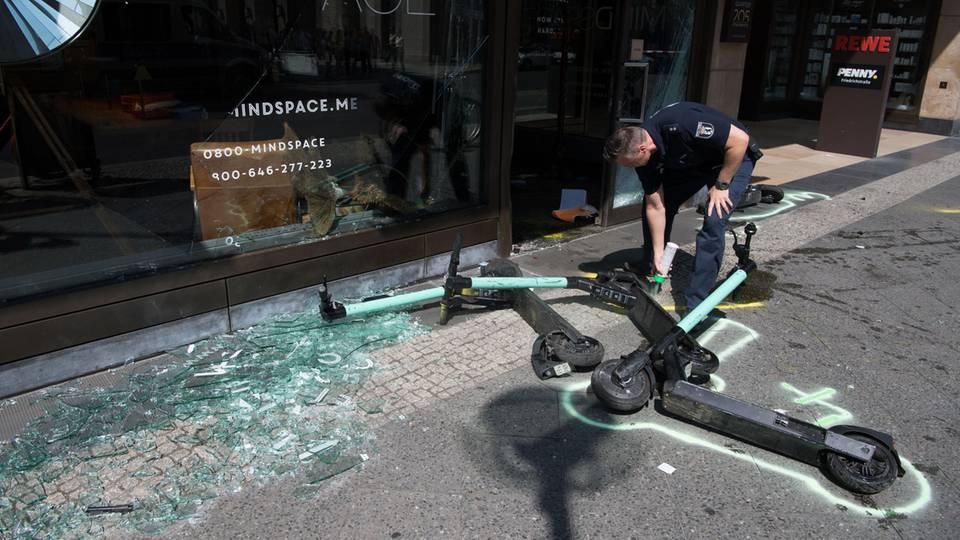 Ein Polizist markiert nach einem Verkehrsunfall in der Mohrenstraße E-Scooter