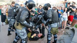 In Moskau liegt ein Mann am Boden, um ihn herum stehen Polizisten