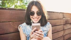 Eine junge Frau schaut grinsend auf ihr Handy