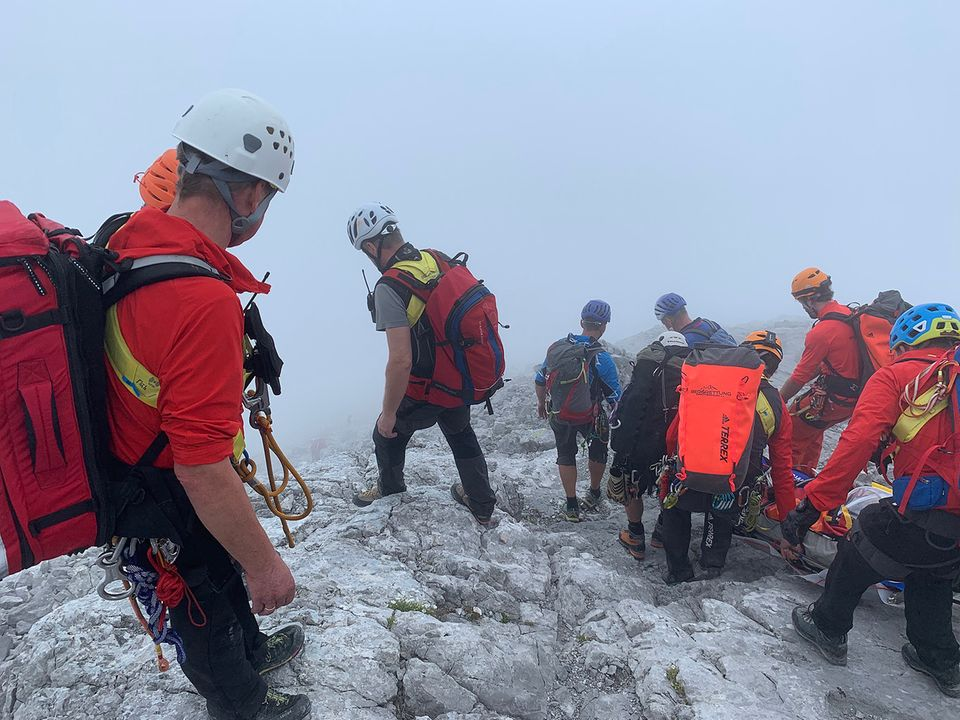 Bergretter bringen die verunglückte Bergsteigerin auf einer Trage in Sicherheit