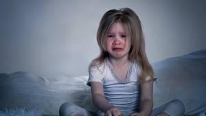 Kleines Mädchen sitzt weinend im Bett