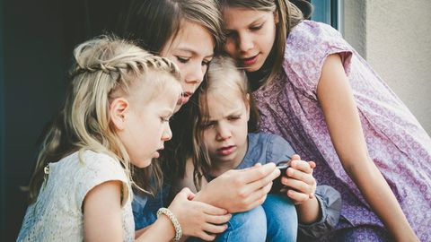 Schwestern unterschiedlichen Alters schauen gemeinsam auf ein Smartphone