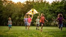 Sechs Kinder lassen einen Drachen steigen